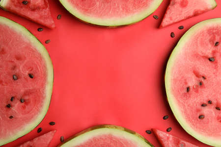 Frame made with slices of ripe watermelon on red background, flat lay. Space for text