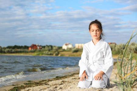 Cute little girl in kimono meditating near river. Karate practicing