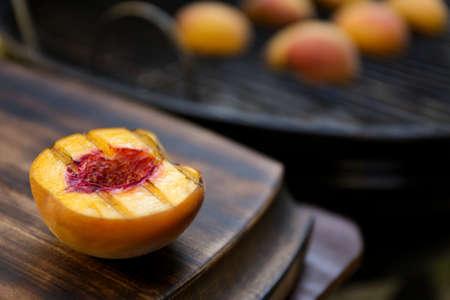一半美味的烤桃子放在木桌上,特写