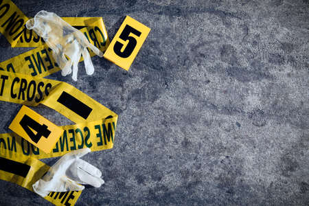 Crime scene markers, tape and gloves on gray stone table, flat lay