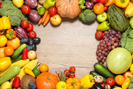 Frame of assorted fresh organic fruits and vegetables on wooden table, flat lay. Space for text