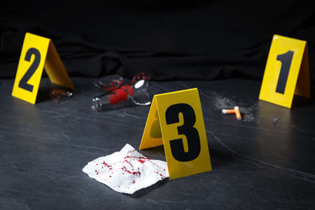 Bloody napkin and crime scene marker on black slate table