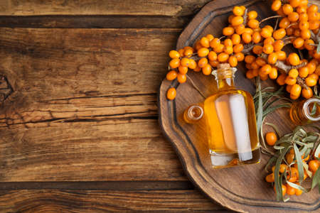 Natural sea buckthorn oil and fresh berries on wooden table, top view. Space for text