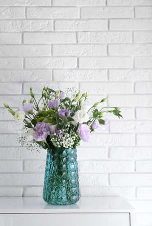 Bouquet of beautiful Eustoma flowers on cabinet near white brick wall
