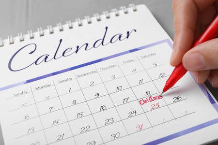 Woman writing word Christmas on calendar, closeup. Holiday countdown 版權商用圖片