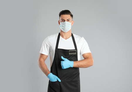 Waiter wearing medical face mask on light gray background