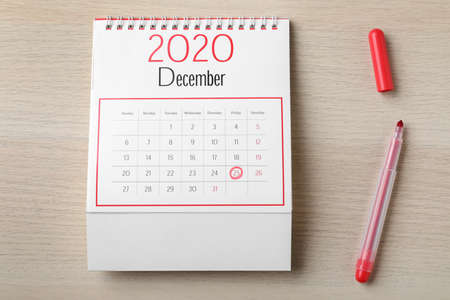 Calendar with marked date and red marker on wooden table, flat lay. Christmas countdown