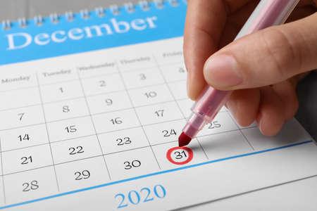 Woman marking date in calendar, closeup. New year countdown