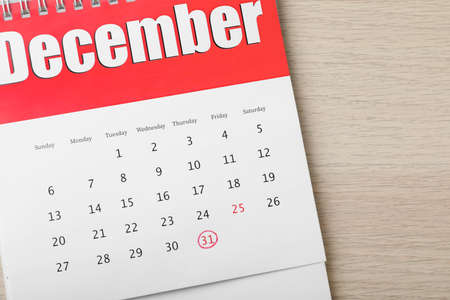 Calendar with marked date on table, top view. New year countdown