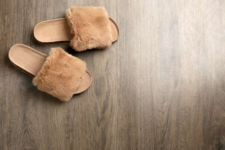 Pair of soft slippers on wooden background, flat lay. Space for text Reklamní fotografie