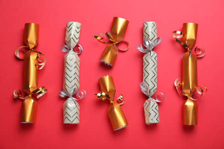 Bright Christmas crackers on red background, flat lay