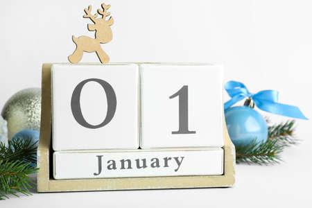 Block calendar and Christmas decor on white background. New Year celebration
