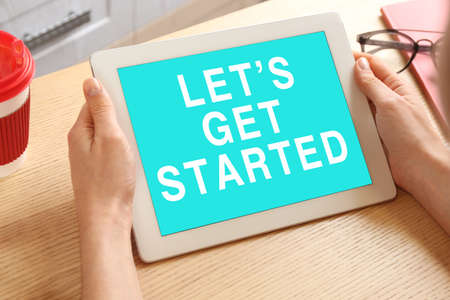 Woman using tablet with phrase Let's Get Started at table, closeup 写真素材