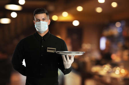 Waiter in medical face mask holding tray in restaurant