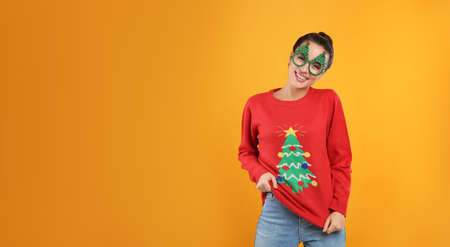 Young woman in Christmas sweater and party glasses on yellow background, space for text Stock Photo