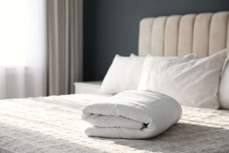 Folded clean blanket on bed in room