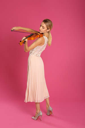 Beautiful woman playing violin on pink background