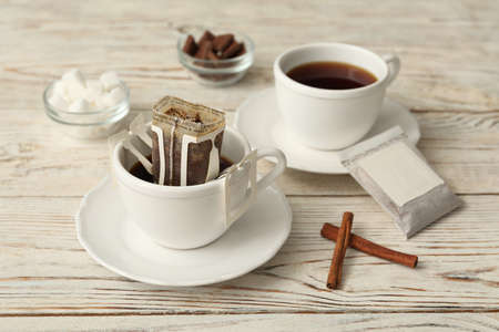 Cup with drip coffee bag and cinnamon on white wooden table