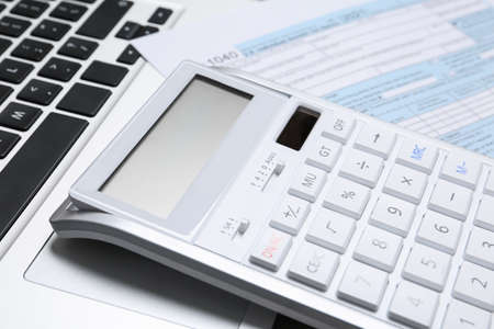 Calculator and document on laptop, closeup. Tax accounting