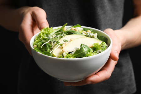 Woman holding bowl with fresh pear salad, closeup