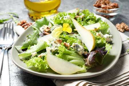Fresh salad with pear served on gray table