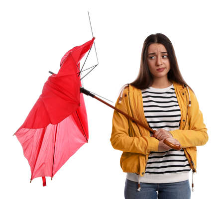 Emotional woman with umbrella broken by gust of wind on white background