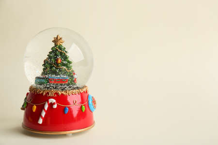 Beautiful snow globe with Christmas tree on beige background, space for text Reklamní fotografie