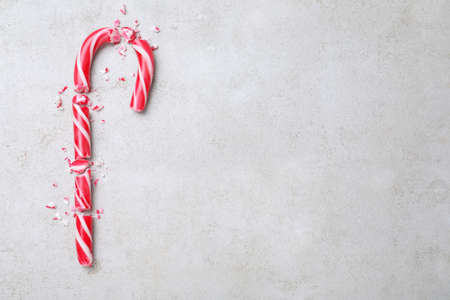 Crushed Christmas candy cane on gray background, flat lay. Space for text