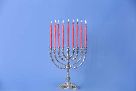 Silver menorah with burning candles on light blue background. Hanukkah celebration