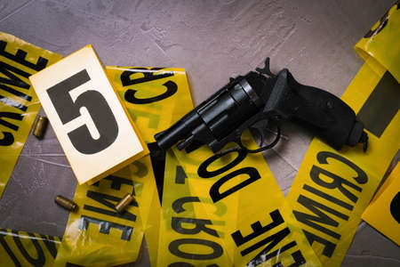 Flat lay with yellow tape, crime scene marker and gun on gray stone background