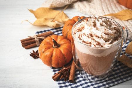Delicious pumpkin latte on white table, closeup