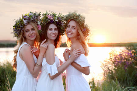 Young women wearing wreaths made of beautiful flowers outdoors at sunset