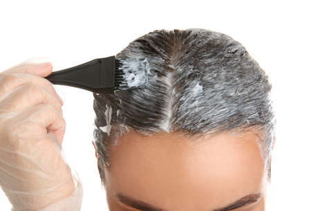 Young woman applying dye on hairs against white background, closeup