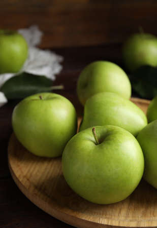 Fresh ripe green apples on wooden tray, closeup