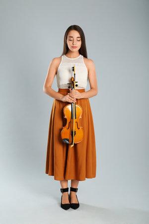 Beautiful woman with violin on gray background Standard-Bild