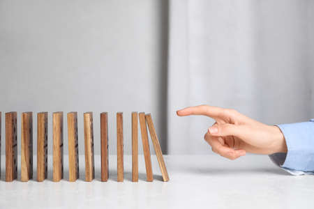 Woman with wooden dominoes at white table, closeup