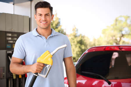 Man with fuel pump nozzle at self service gas station