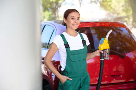 Young worker with fuel pump nozzle near car at modern gas station