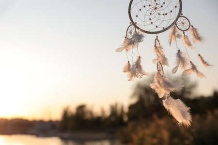 Beautiful handmade dream catcher near river on sunny day. Space for text