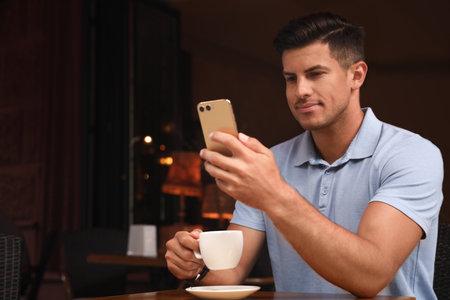 Man unlocking smartphone with facial scanner in cafe. Biometric verification Reklamní fotografie