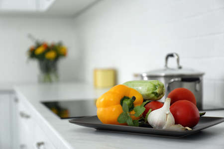 Different fresh vegetables on countertop in modern kitchen. Space for text Stock Photo