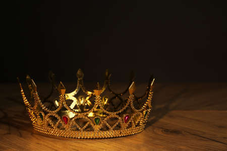 Beautiful golden crown with gems on wooden table. Fantasy item
