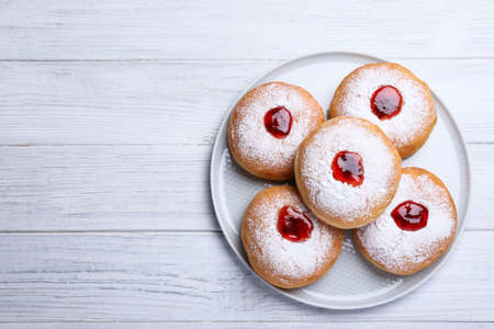 Hanukkah donuts with jelly and sugar powder on white wooden table, top view, Space for text