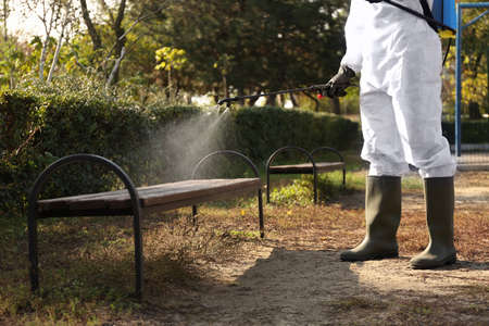 Person in hazmat suit spraying disinfectant onto bench outdoors, closeup. Surface treatment during coronavirus pandemic