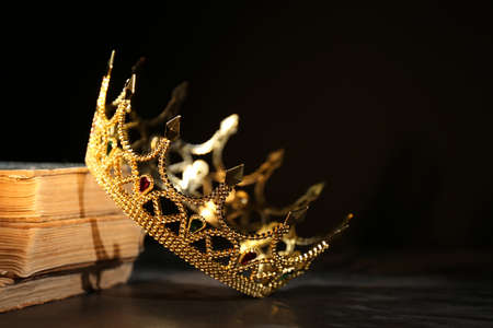 Beautiful golden crown and old books on black table. Fantasy item