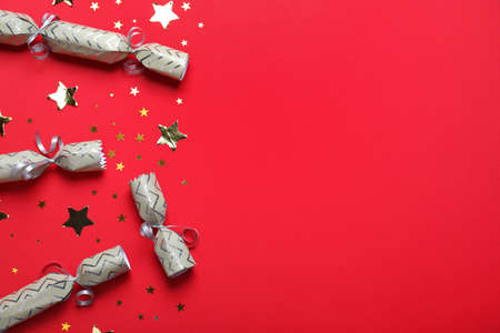 Open and closed Christmas crackers with shiny confetti on red background, flat lay. Space for text
