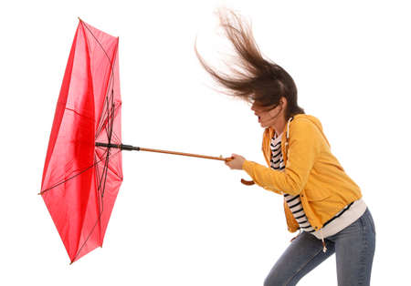 Woman with umbrella caught in gust of wind on white background