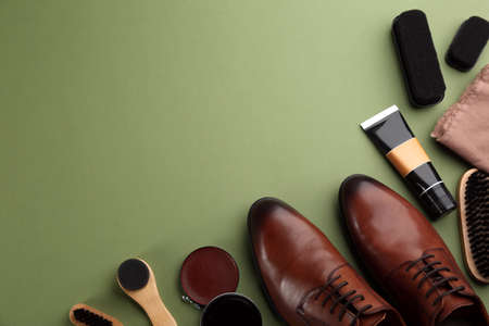 Flat lay composition with shoe care accessories and footwear on green background. Space for text