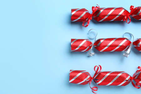 Red Christmas crackers on light blue background, flat lay. Space for text