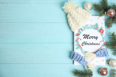 Flat lay composition with Christmas card and festive decor on light blue wooden background, space for text